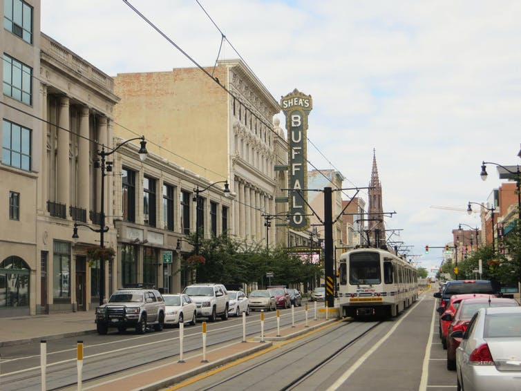 A city street with cars parked on the sides, lined with a theater and other buildings.