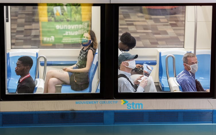 People sit on a Montreal metro wearing face masks