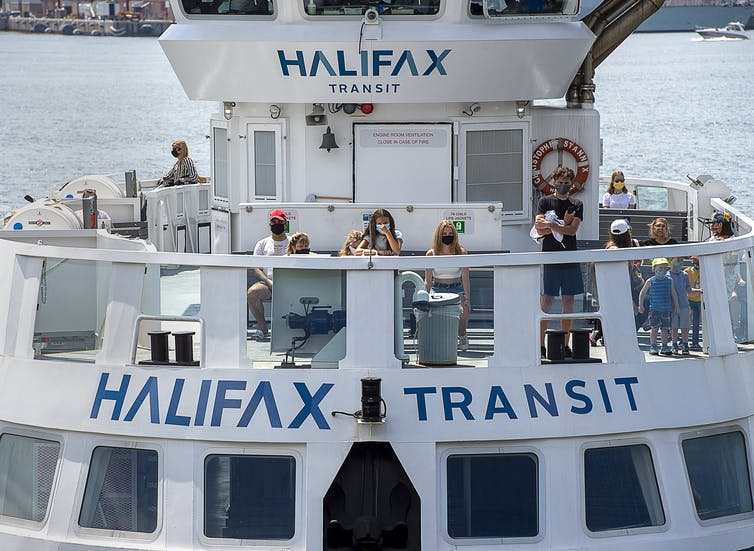 Passengers wear face masks on a Halifax Transit ferry. Ferry is seen with a dozen passengers on the top deck, Halifax harbour peaks through the background.